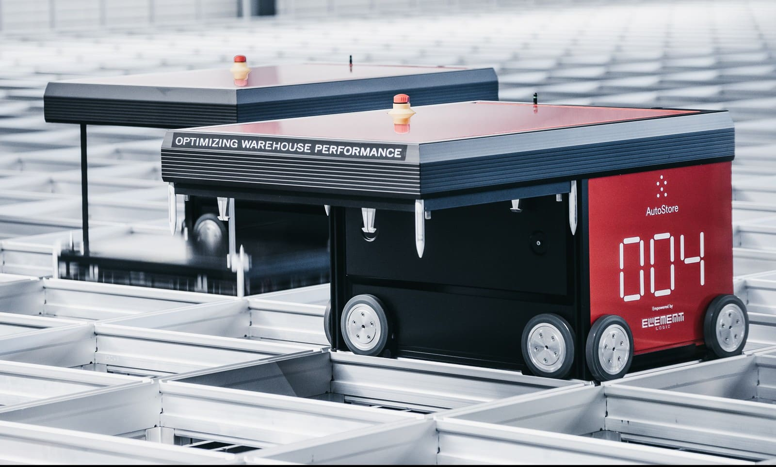 Red AutoStore R5-robots working in warehouse.